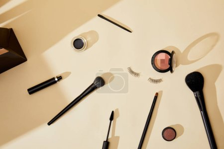 top view of various cosmetics and false eyelashes lying on beige tabletop