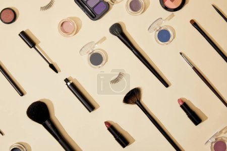 top view of composition of different cosmetics lying on beige surface