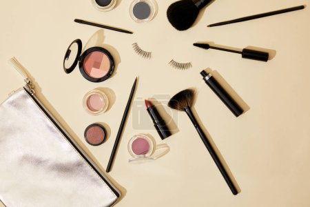 top view of various cosmetics lying on beige surface around false eyelashes