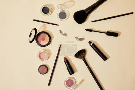 Photo pour Vue de dessus de différents cosmétiques couchés sur une surface beige autour de faux cils - image libre de droit