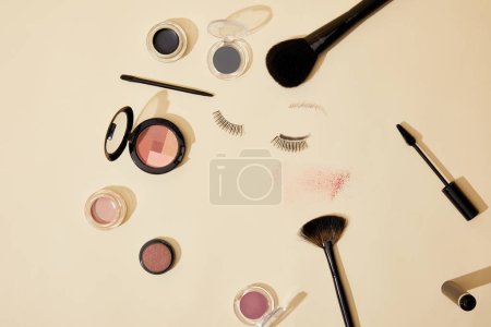 top view of various cosmetics lying on beige surface