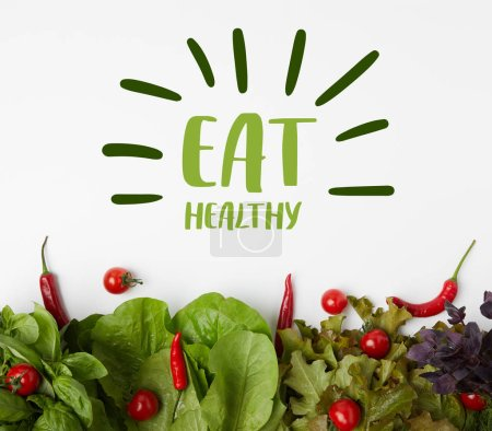 "top view of fresh various leaf vegetables with tomatoes and peppers on white surface with ""eat healthy"" lettering"