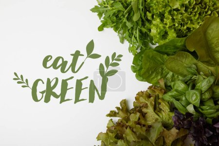"top view of fresh various leaf vegetables on white surface with ""eat green"" lettering"