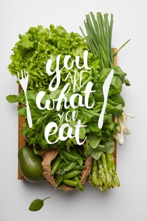 "top view of various ripe vegetables in box on white surface with ""you are what you eat"" inspiration"