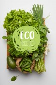 """top view of various ripe vegetables in box on white surface with """"eco product"""" lettering"""