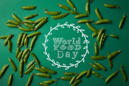 "top view of round frame made of pea pods on green surface with ""world food day"" lettering"