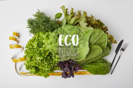 "Photo for Top view of various ripe vegetables in box with cutlery and measuring tape on white surface with ""eco product"" lettering - Royalty Free Image"