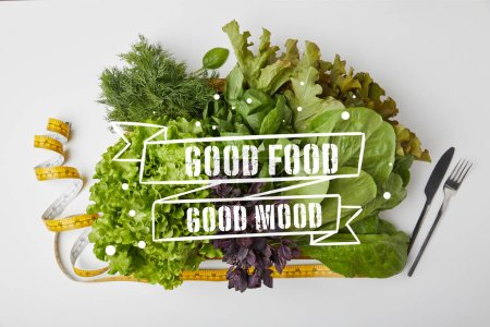 "top view of various ripe vegetables in box with cutlery and measuring tape on white surface with ""good food - good mood"" inspiration"