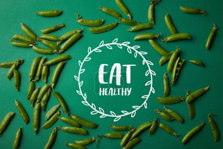 "Photo for Top view of round frame made of pea pods on green surface with ""eat healthy"" lettering - Royalty Free Image"