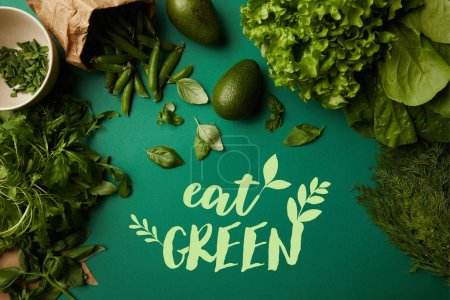 "Photo for Top view of different ripe vegetables on green surface with ""eat green"" lettering - Royalty Free Image"