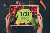 "cropped image of woman holding wooden box with vegetables above gray table with ""eco product"" lettering"