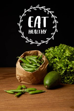 """close-up shot of avocado, green peas and lettuce on wooden surface with """"eat healthy"""" lettering"""
