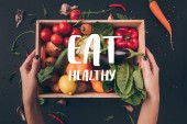 "cropped image of woman holding wooden box with vegetables above gray table with ""eat healthy"" lettering"