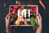 """imagen recortada de la mujer que sostiene la caja de madera con verduras por encima de la mesa gris con letras """"comer sano"""""""