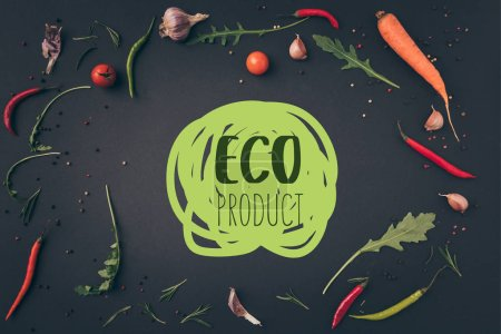 "top view of arugula, carrot and chili peppers on gray surface with ""eco product"" lettering"