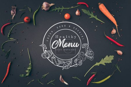 "top view of arugula, carrot and chili peppers on gray surface with ""healthy menu"" lettering in seal"