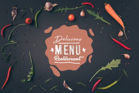 "Photo for Top view of arugula, carrot and chili peppers on gray surface with ""delicious menu restaurant"" lettering - Royalty Free Image"