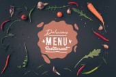 """top view of arugula, carrot and chili peppers on gray surface with """"delicious menu restaurant"""" lettering"""