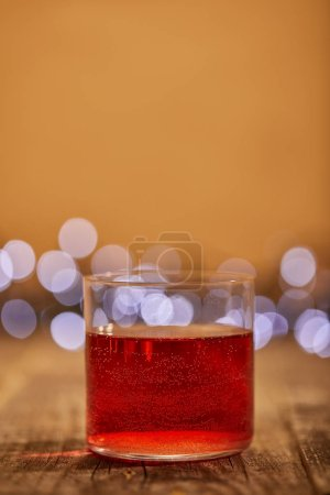 close up view of tasty mulled wine in glass on wooden surface with defocused bokeh lights on backdrop