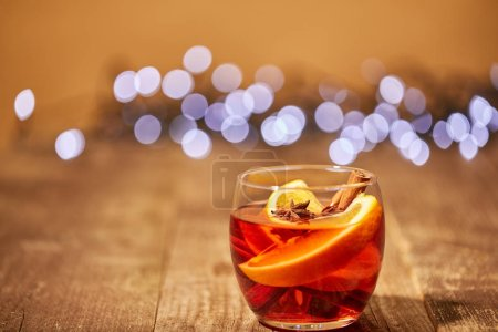Photo for Close up view of mulled wine drink with orange pieces and anise stars on wooden surface with bokeh lights on background - Royalty Free Image