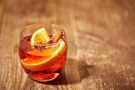 Photo pour Vue rapprochée de la boisson chaude au vin chaud chaud avec des morceaux d'orange et des étoiles d'anis sur la surface en bois - image libre de droit