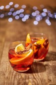 close up view of mulled wine in glasses with orange pieces and spices on wooden surface with bokeh lights on backdrop