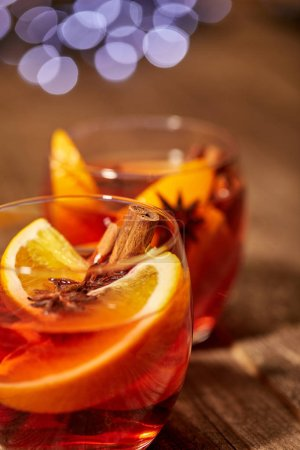 close up view of hot mulled wine drinks with spices and orange pieces on wooden tabletop with blurred bokeh lights on backdrop