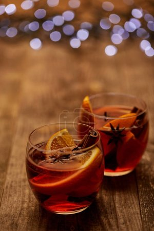 close up view of delicious hot mulled wine in glasses with orange pieces on wooden tabletop with bokeh lights on backdrop