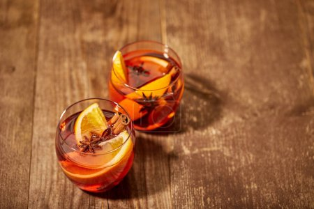 close up view of delicious hot mulled wine drinks with orange pieces on wooden tabletop