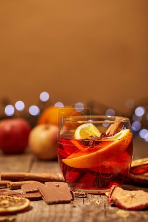 close up view of mulled wine drink, chocolate and spices on wooden surface with bokeh lights on background