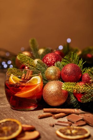 close up view of mulled wine drink in glass and pine tree with christmas toys on wooden surface