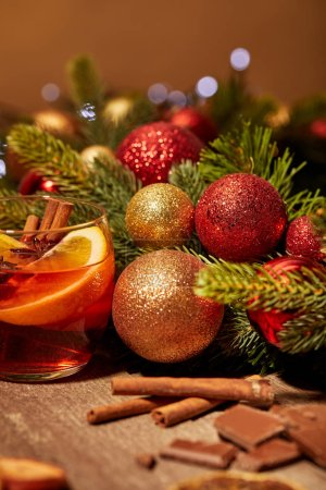 close up view of mulled wine drink in glass, chocolate and pine tree with christmas toys on wooden surface