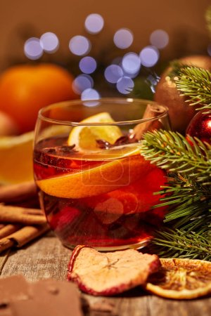 close up view of mulled wine drink with orange pieces and spices on wooden surface with bokeh lights on backdrop