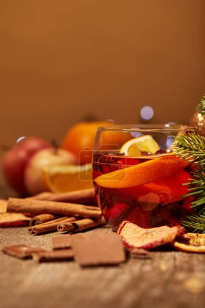 close up view of tasty mulled wine drink, chocolate and pine tree branch on wooden surface