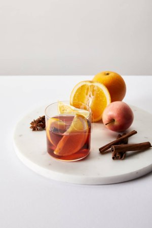 close up view of hot mulled wine in glass fresh oranges and apple on white surface on grey backdrop