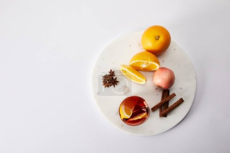 top view of hot mulled wine in glass, spices, oranges and apple on white surface
