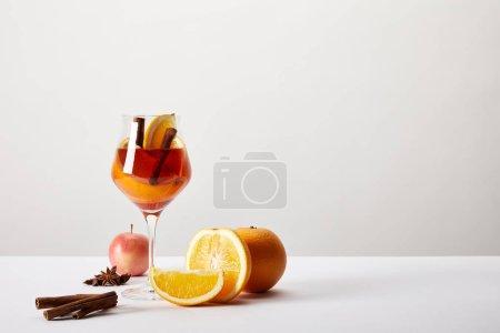 Photo pour Bouchent la vue de vin chaud en verre et ingrédients disposés autour sur table blanc sur fond gris - image libre de droit