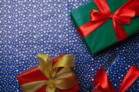 flat lay with wrapped gifts with ribbons on wrapping paper with stars pattern