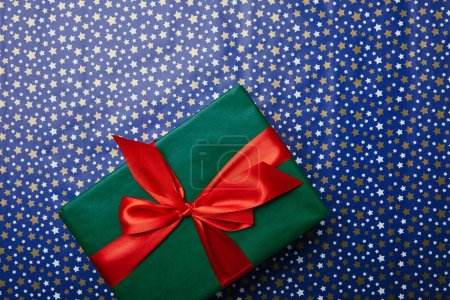 top view of green gift with red ribbon on festive wrapping paper with stars pattern