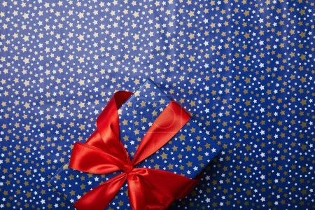 top view of wrapped gift box with red ribbon on festive wrapping paper with stars pattern