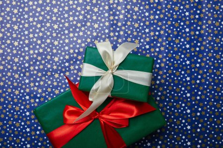 top view of wrapped new year presents with ribbons on wrapping paper with stars pattern