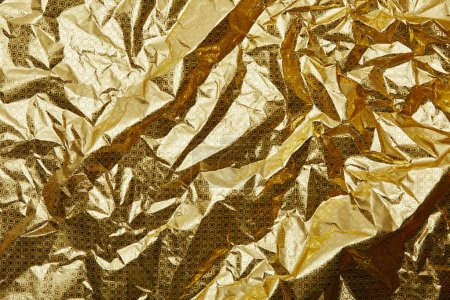 full frame of shiny crumpled golden wrapping paper as background