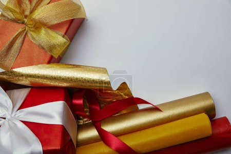 top view of presents with ribbons and bright wrapping papers on white backdrop
