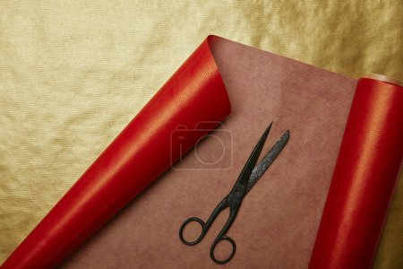 top view of scissors on red and golden wrapping papers background
