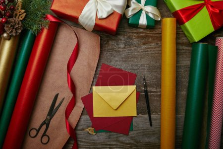 flat lay with different wrapping papers, chrtismas toys on pine tree branch, wrapped presents and blank envelopes on wooden tabletop