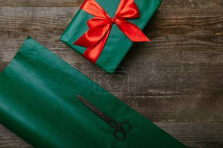 top view of green wrapping paper, scissors and present with red ribbon on wooden background