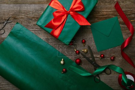 top view of christmas toys, wrapped present with ribbon and blank envelope for greeting card on wooden background