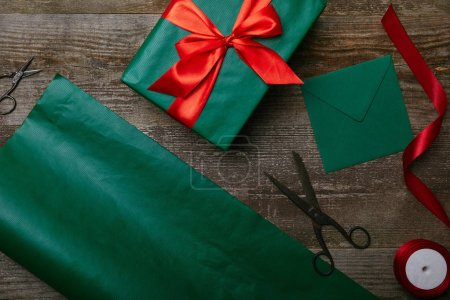 top view of wrapped christmas gift, scissors, blank envelope and green wrapping paper on wooden background