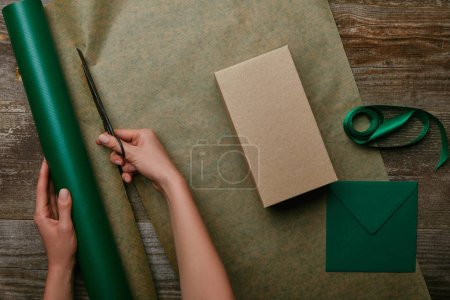 partial view of woman cutting wrapping paper with scissors on wooden surface with gift and envelope