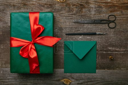 flat lay with wrapped christmas gift with red ribbon, scissors and envelope for greeting card on wooden surface